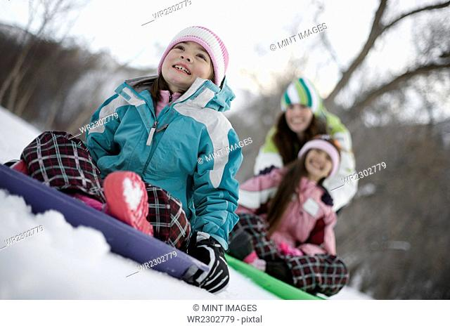 Two children playing on sledges, on the snow