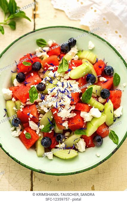 Watermelon salad with blueberries, feta, cucumber, basil and cornflower blossoms