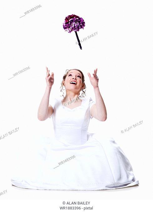 Happy bride throwing bouquet, studio shot