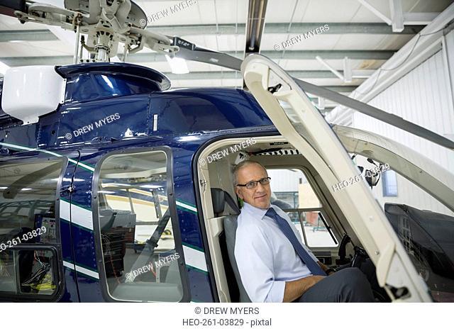 Portrait confident pilot in helicopter cockpit