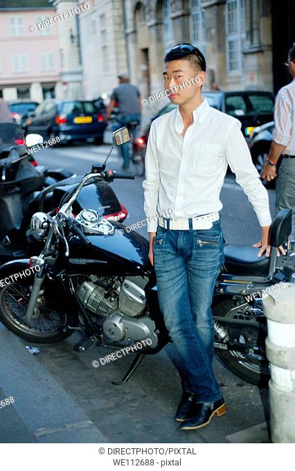 Paris, France, Young Asian Man Standing by Vintage Motorcycle on Street in St. Germain des Prés District