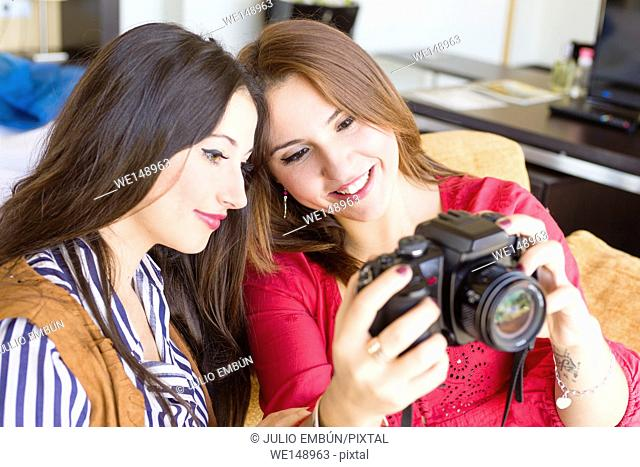 Two young women with their camera on the couch of their house in the morning