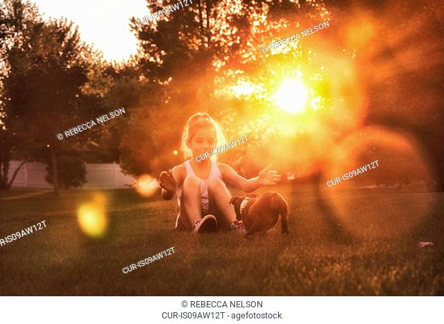 Girl sitting on grass arms open encouraging Boston terrier puppy