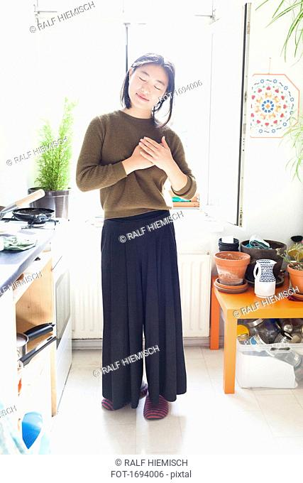 Full length of young woman with hands clasped standing against window in kitchen