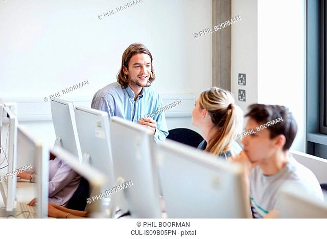Male lecturer talking to student in higher education college computer room