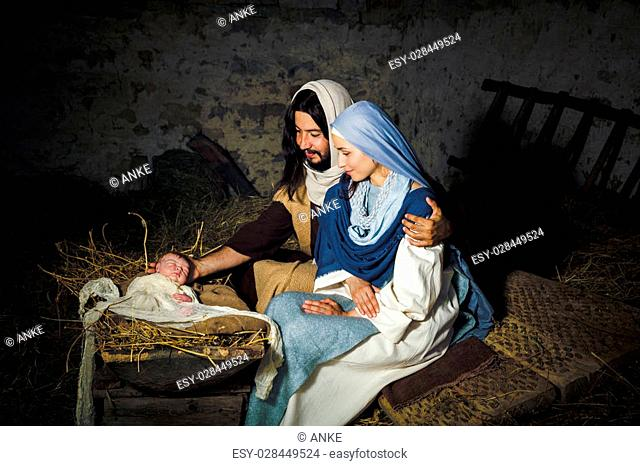 Live Christmas nativity scene in an old barn - Reenactment play with authentic costumes. The baby is a (property released) doll