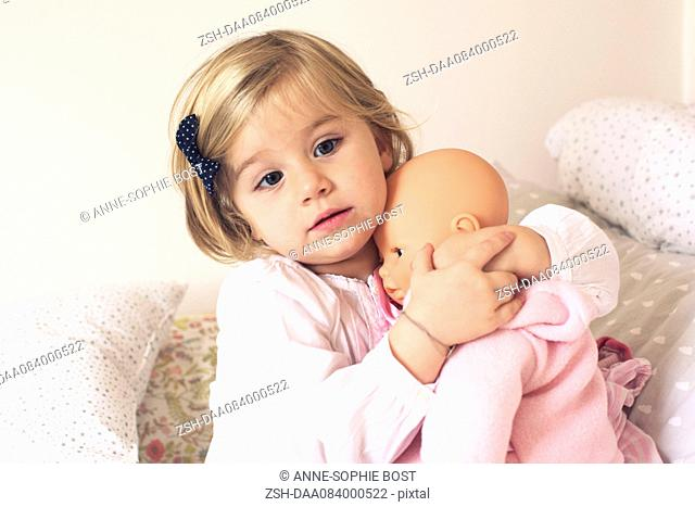 Little girl hugging doll
