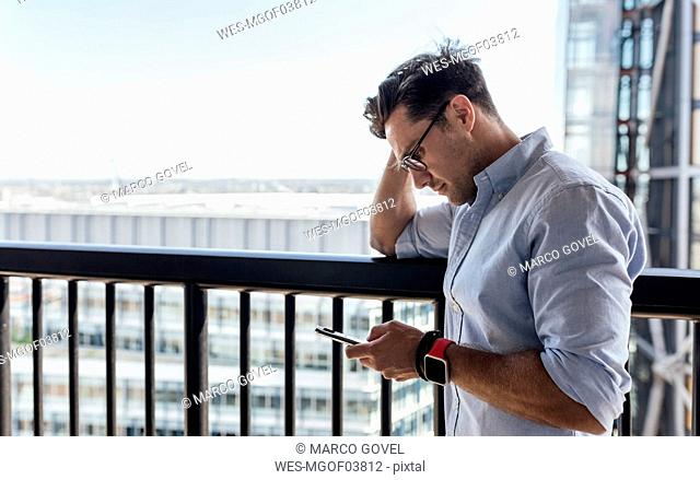 UK, London, man using cell phone on a roof terrace