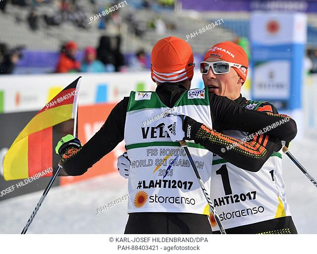 Johannes Rydzek (1st Place) and Eric Frenzel (r, 2nd Place), both from Germany, celebrate after the single combination event normal hill/10 km during the...