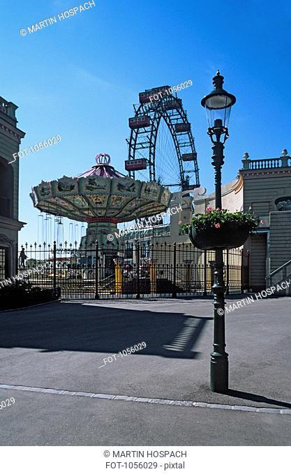 Austria, Vienna, Prater park amusement park rides with lamp post in foreground