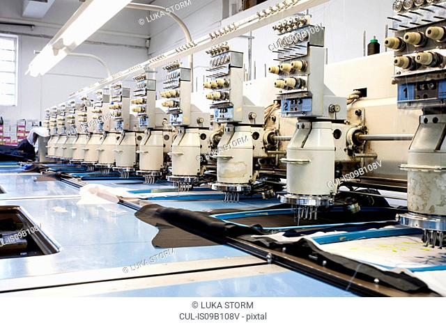 Rows of programmed embroidery machines speed stitching in clothing factory