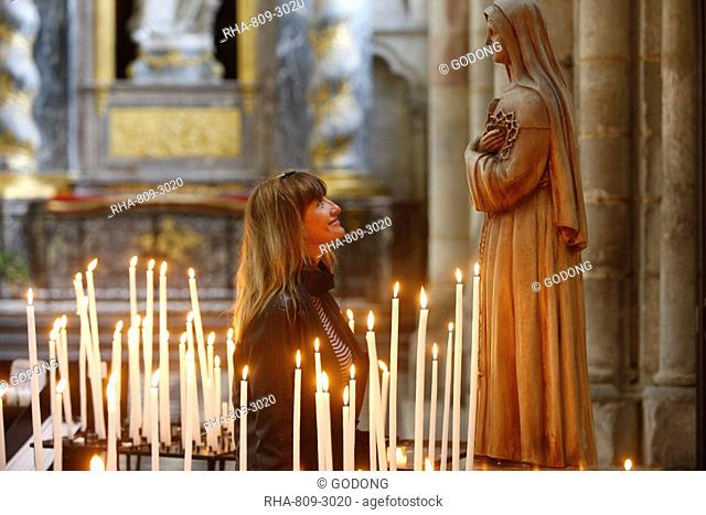 Woman praying to Santa Rita, Amiens Cathedral, Somme, France, Europe