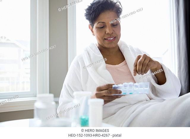 Woman in bathrobe organizing pill box