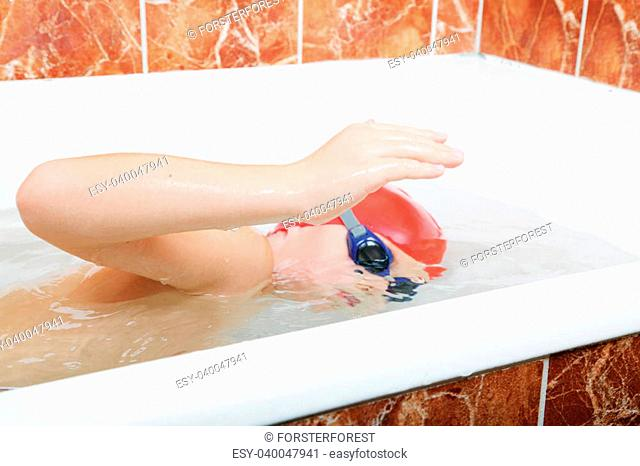 Little boy in cap and goggles crowl swimming in bath