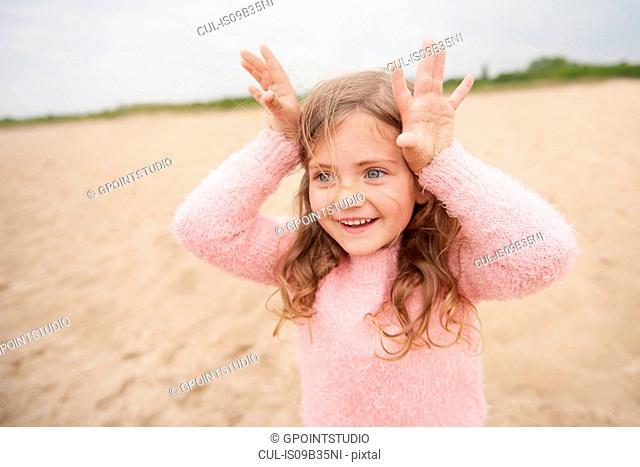 Little girl showing horns on head at beach