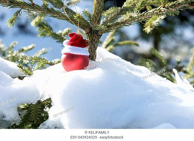 Red Christmas tree ball on the snow covered fir tree
