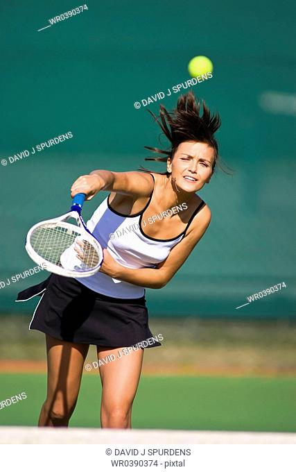 Tennis player volleys ball over net