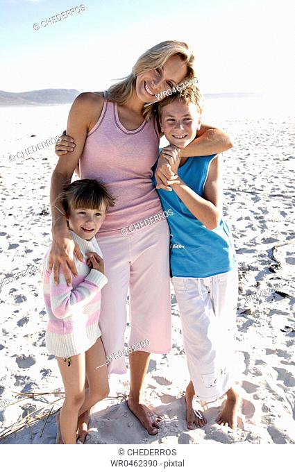 Portrait of a mid adult woman with her son and daughter standing on the beach