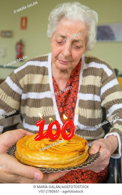 Old woman in a nursing home, on her one hundred birthday, blowing birthday's candles on a cake held by a man's hands