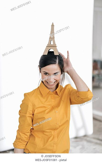 Young woman with model of the Eiffel Tower planning trip to Paris