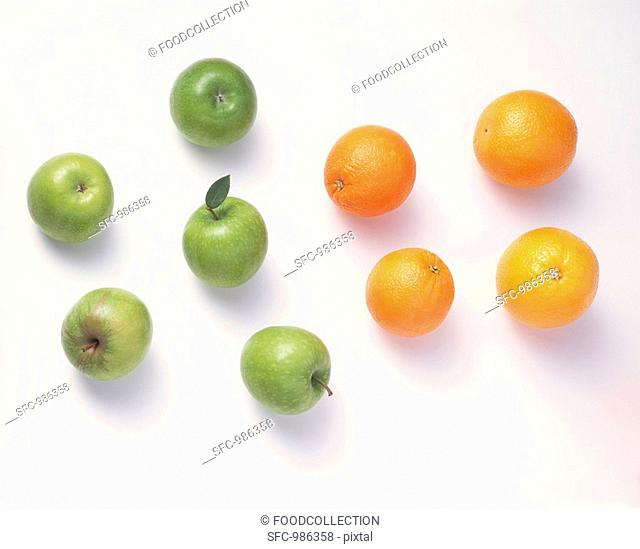 Five green apples & four oranges against a white background