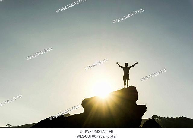 Silhouette of happy man standing on a rock at backlight