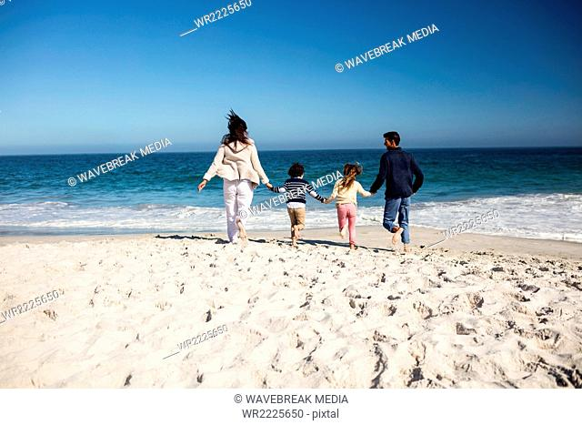 Cute family holding hands and running