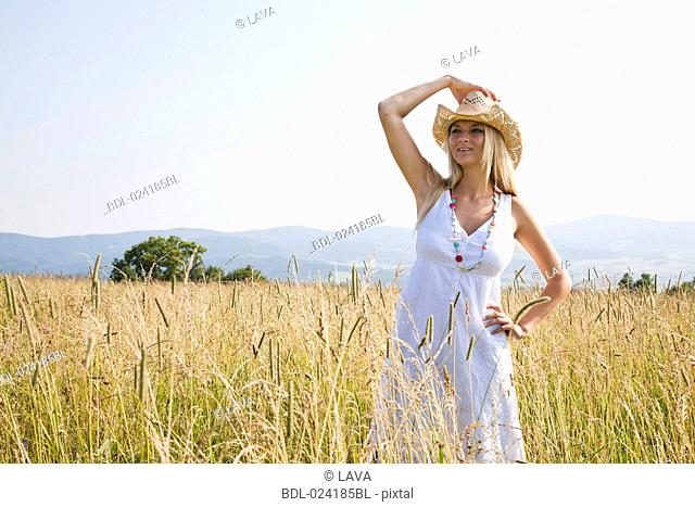 young woman with hat standing in field