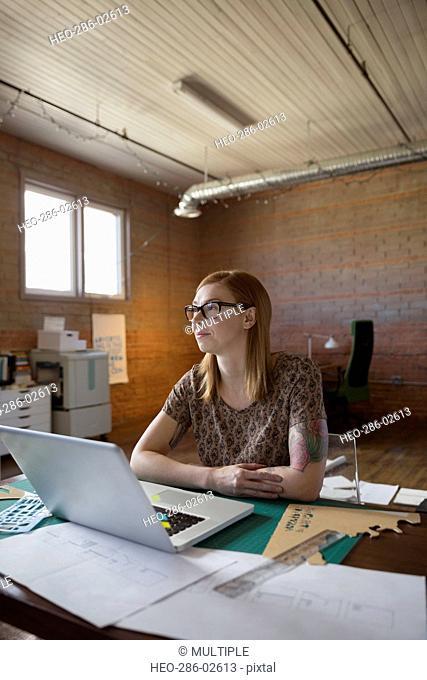 Pensive female designer at laptop looking away