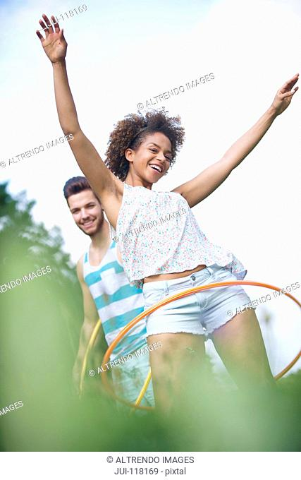 Portrait Of Young Couple Playing With Hula Hoops Outdoors