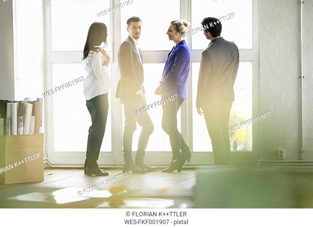 Group of successful business people standing at window