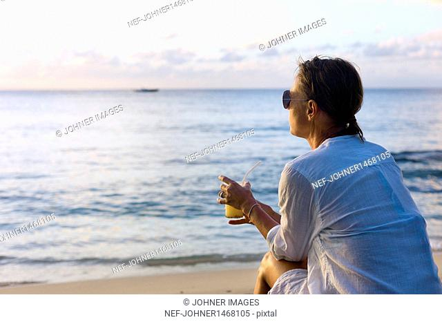 Woman drinking cocktail on beach