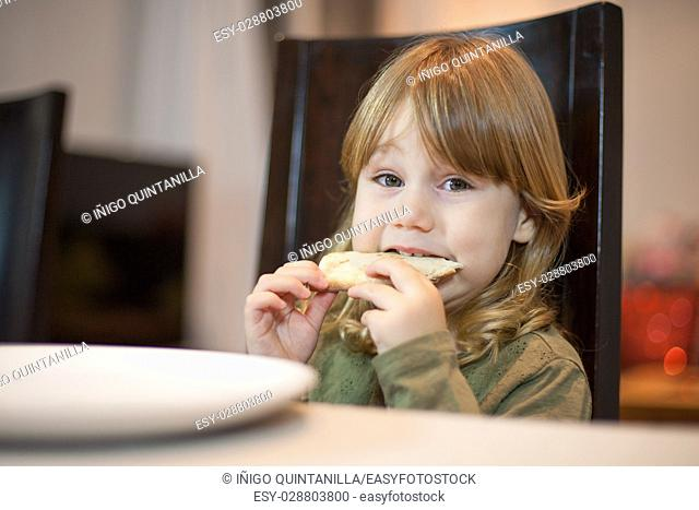 Three years old blonde hungry child biting pizza piece in her hands, sitting in dark brown chair, in table with grey tablecloth at home, looking at camera