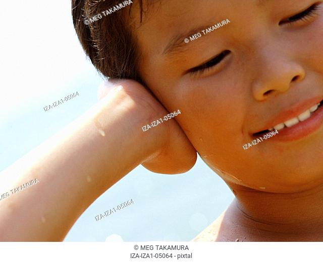 Close-up of a boy covering his ears