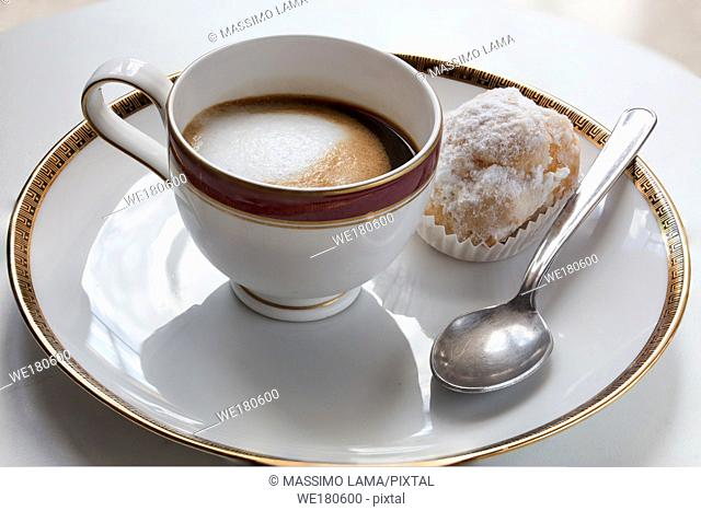 coffee with milk and biscuit in saucer, close up