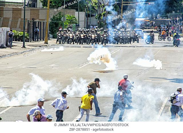 Bolivarian National Police, lashes out against protesters with tear gas in the streets near the highway. Opponents marched to the Ombudsman's Office