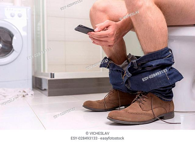 Man wearing jeans and shoes using phone while sitting on a toilet bowl in the modern tiled bathroom at home