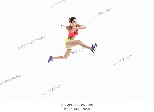 Side view of female athlete jumping