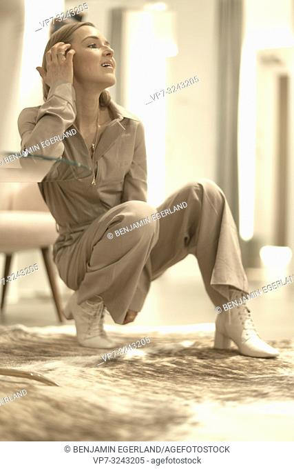 sensual woman crouching indoors on carpet floor in clothing store, desire for women's fashion trends, wearing beige one-piece jumpsuit, in Munich, Germany
