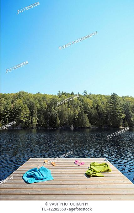 0918701a4 Towel and flip flops by lake Stock Photos and Images