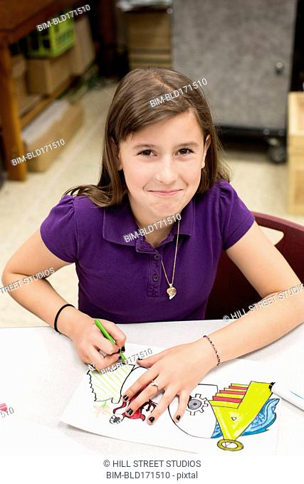 Caucasian student coloring at desk in classroom