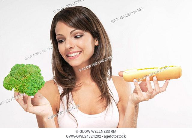 Woman choosing between broccoli and a hot dog