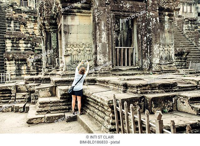 Caucasian tourist photographing Angkor Wat ruins, Siem Reap, Cambodia
