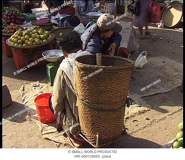 Woman buying chillis at tradidtional market. Laos