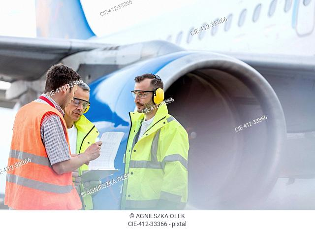 Air traffic control ground crew with clipboard next to airplane on tarmac