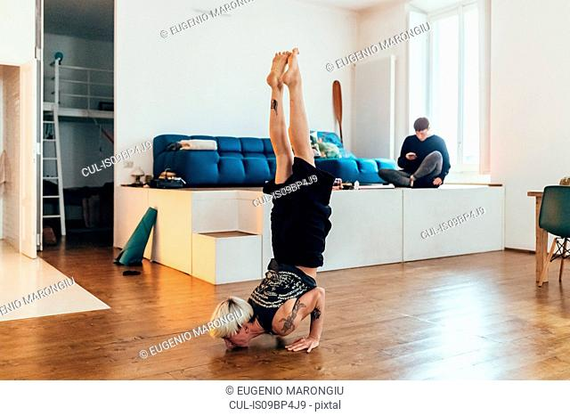 Woman practising yoga at home, friend in background