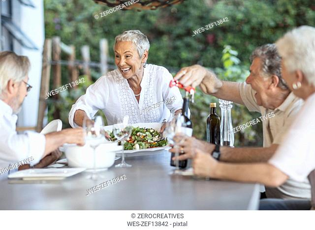 Smiling senior woman serving lunch on terrace