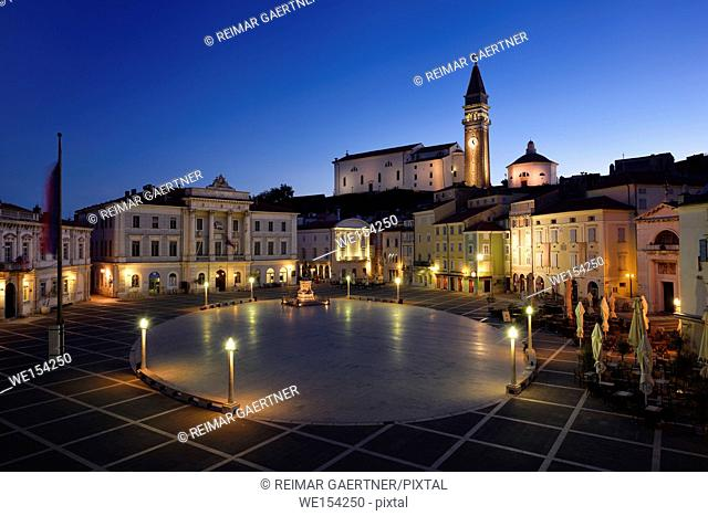 Empty Tartini Square in Piran Slovenia with Courthouse, City Hall, statue, St. George's Parish Church with baptistry, and St Peter's church at dawn