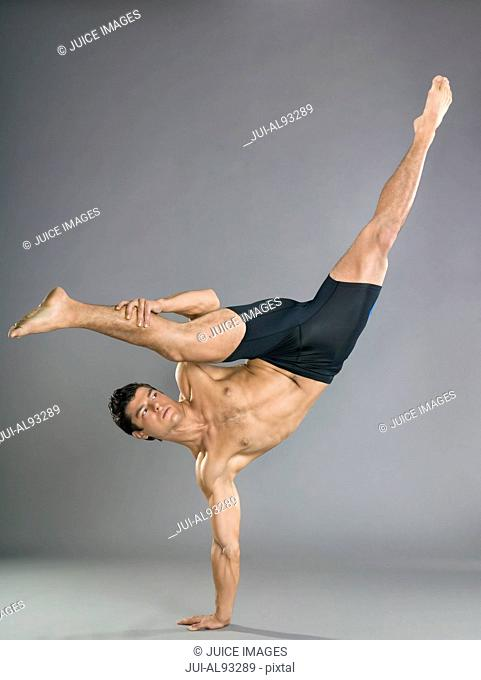 Bare-chested man balancing on one hand