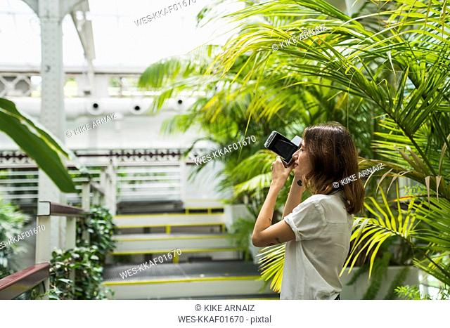 Young woman in greenhouse, taking pictures with an instant camera